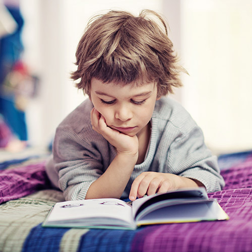 a photo of young boy lying on a bed reading a book